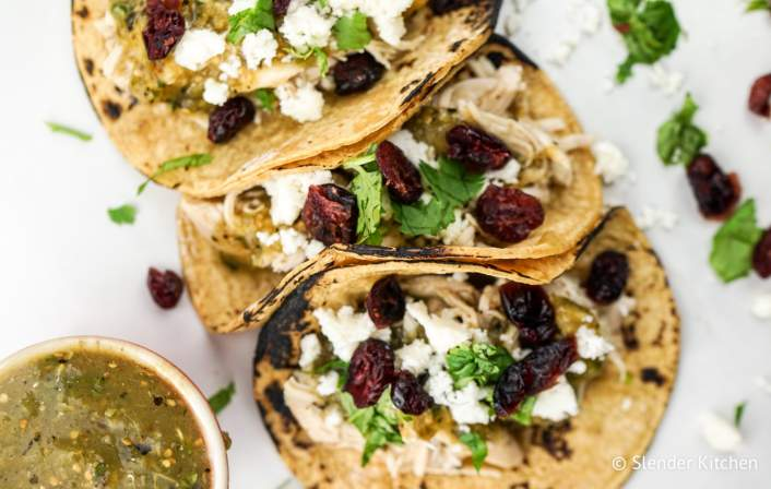 Slow Cooker Turkey Tacos with cilantro, onion, and cranberries on tortillas