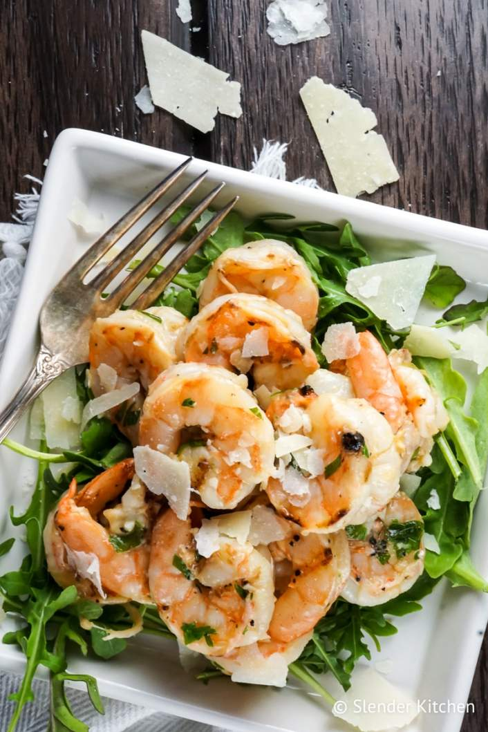 Garlic Parmesan Shrimp fresh out of the oven over a bed of greens.
